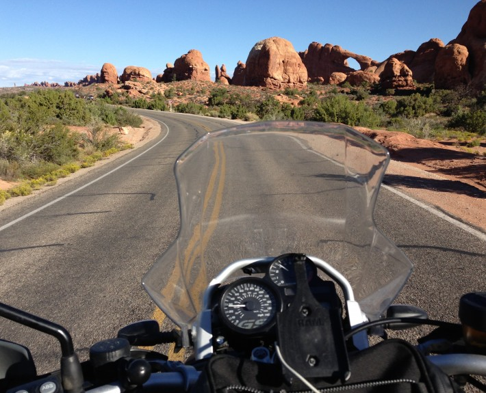 Scott G. Nelson riding past Landscape Arch in Arches National Park